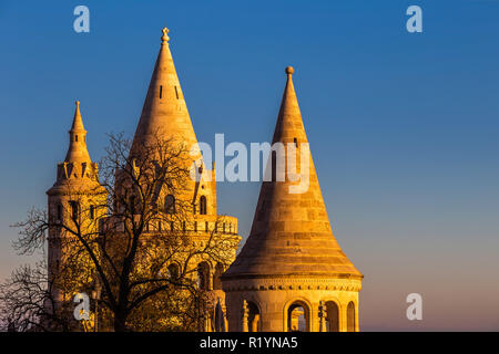Budapest, Hungary - Towers of the famous Fisherman's Bastion (Halaszbastya) on a golden sunny autumn morning with clear blue sky - Stock Image