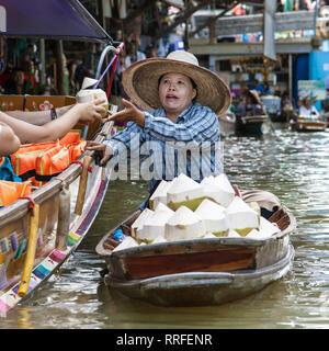 Damnoen Saduak, Thailand - August 29, 2018: Woman selling coconuts from a boat in Damnoen Saduak Floating Market, Ratchaburi, Thailand. - Stock Image
