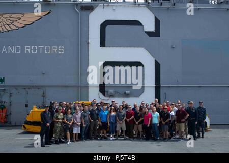 "180824-N-XT039-1211 SAN DIEGO (Aug. 24, 2018) Marines, assigned to the ""Guardians"" of Headquarters and Headquarters Squadron Marine Corps Air Station (MCAS) Yuma, and Sailors, assigned to the amphibious assault ship USS Bonhomme Richard (LHD 6), pose for a group photo on the ship's flight deck during a ship tour. The tour provided an opportunity for Marines of MCAS Yuma to experience a Navy ship and learn about amphibious operations. Bonhomme Richard is in its homeport of San Diego. (U.S. Navy photo by Mass Communication Specialist 3rd Class Jesse Marquez Magallanes) - Stock Image"