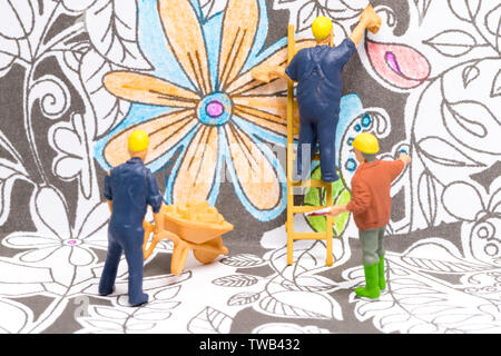 Macro shot on miniature figures as painters working on colouring details on a wallpaper - Stock Image
