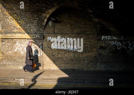 Asian woman walks past graffiti in London's Bethnal Green welcoming migrants. - Stock Image