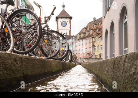 Freiburg im Breisgau, Germany - Schwabentor (Swabian city gate), bicycles, and Bachle (water filled runnels fed by the Dreisam), Germany, Europe - Stock Image