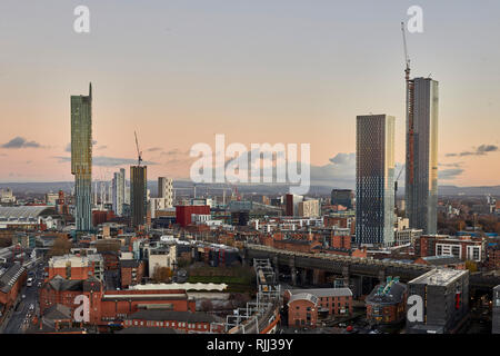 Manchester city centre skyline view across the rooftops from Salford  Beetham Tower and Deansgate Square  skyscraper cluster development currently und - Stock Image