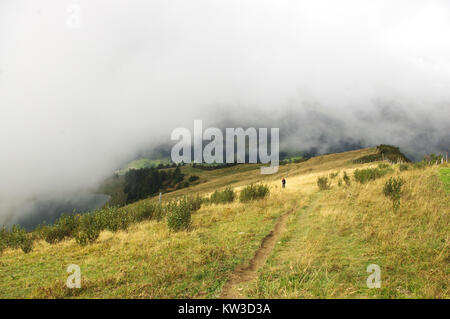 Gryon, Switzerland, Sep 16th 2017. Mists settle on Chaux Ronde as a hiker follows the trail up. - Stock Image