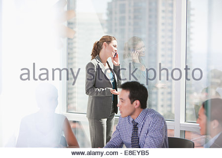 Businesswoman talking on cell phone in meeting - Stock Image