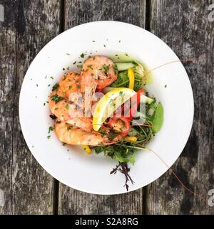 Looking down from above onto a seafood platter with fresh prawns in their shells and salad leaves at a restaurant - Stock Image