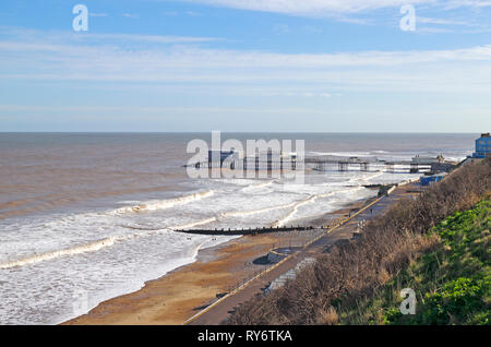 A view of the beach and pier with a moderate sea in winter on the North Norfolk coast at Cromer, Norfolk, England, United Kingdom, Europe. - Stock Image