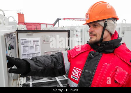 Kogalym, Russia. 21st Mar, 2019. KOGALYM, RUSSIA - MARCH 21, 2019: A worker wearing a hard hat at the Yuzhno-Yagunskoye oil field developed by Kogalymneftegaz, a subsidiary of the Lukoil-West Siberia oil and gas company. Vyacheslav Prokofyev/TASS Credit: ITAR-TASS News Agency/Alamy Live News - Stock Image