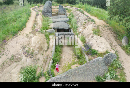 Little boy visitor discovering Dolmen of Lacara, Ancient megalithic building,  Extremadura. Spain. Aerial view - Stock Image