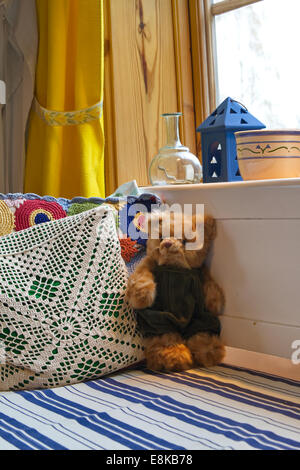 A teddy bear is sitting on an old fashioned wooden sofa. - Stock Image