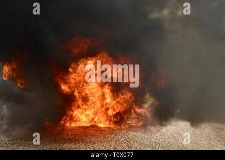 Explosive, dangerous inferno fire with undulating, dancing flames and blackening smoke rising and billowing cloud and plumes of smoke. - Stock Image
