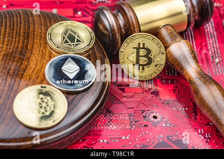 Different cryptocurrencies and gavel over computer mainboard.Concept image for cryptocurrency - Stock Image