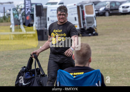 Muddy runner carrying a bag at the end of a mud run - Stock Image