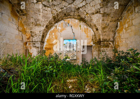 View through a window of a medieval, cracked stone wall of the ancient Madonna de Idris rock church and Sassi of Matera, Italy, in Basilicata region - Stock Image