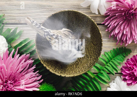 Burning Sage Smudge with Spring Flowers - Stock Image