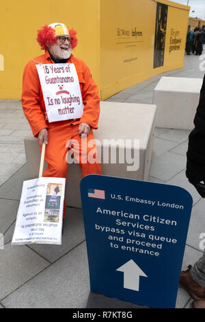 London, UK. 10th December 2018.  A protester talks with people going to the US Embassy in the final 'Shut Guantanamo!' monthly protest of 2018 on the 70th anniversary of the Universal Declaration of Human Rights (UDHR). This declared 'No one shall be subjected to torture or to cruel, inhuman or degrading treatment or punishment' and 'No one shall be subjected to arbitrary arrest, detention or exile.' Guantanamo still has 40 detainees who have been tortured and held in indefinite detention without trial for almost 17 years. Credit: Peter Marshall/Alamy Live News - Stock Image