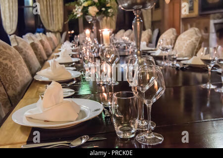 Large dinner table set for formal evening dinner at a stately home. - Stock Image