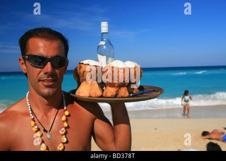 Barman with coconut rum cocktails on Playa Megano, Playas del Este, Havana, Cuba. Photo CUBA1230 Copyright Christopher - Stock Image