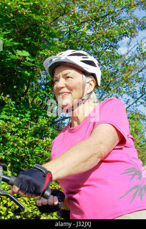 Smiling senior woman with white helmet and protective gloves holding her bicycle on a sunny summer's day, green - Stock Image