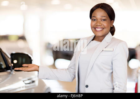 beautiful African car saleswoman presenting new vehicles - Stock Image