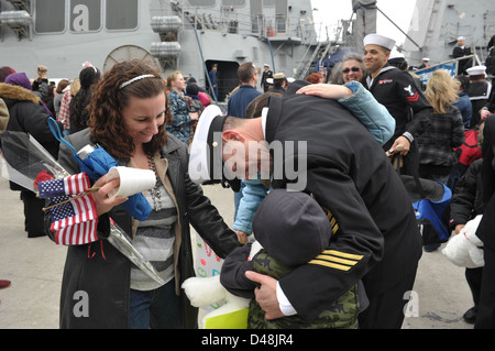 A Sailor is greeted by his family upon returning home from deployment. - Stock Image