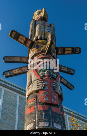 Sun-man holding a Copper, Thunderbird on top, at Kwakwaka'wakw Totem Pole, 1979, by Kwawkewlth Tribe carver - Stock Image