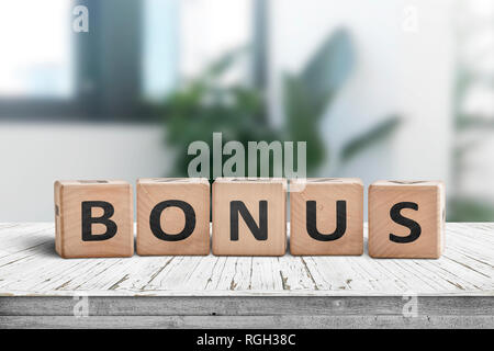 Bonus reward sign on a white table in a bright office with green plants - Stock Image