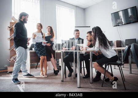 Group of young business people working and communicating together in creative office - Stock Image