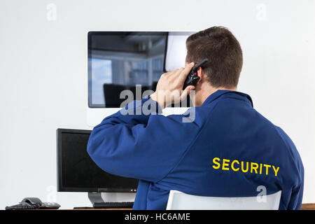 Security officer talking on walkie-talkie while looking at computer monitors - Stock Image