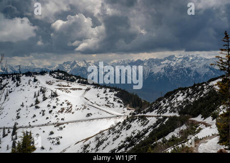 View from Herzogstand trail iin Upper Bavaria in the late Spring, featuring snow and the Alps in the background - Stock Image