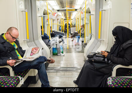 A woman in a burqa  on the London Overground in Britain - Stock Image