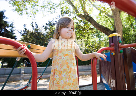 Three years old blonde girl with yellow dress, with thoughtful expression face, playing on wooden construction in outdoor playground, in public park o - Stock Image