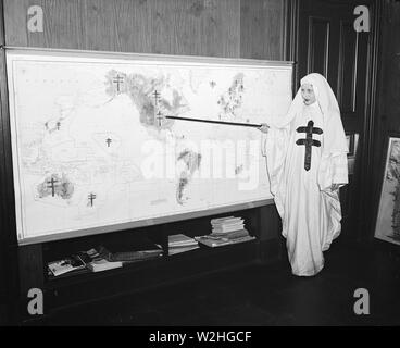 Miss Mildred Showalter of Washington, dressed as the Spirit of the Double-barred cross of the anti- tuberculosis movement throughout the world, points to various battlefronts throughout the world where the fight is being carried on against the 'White Plague.' ca. 11/25/1935 - Stock Image