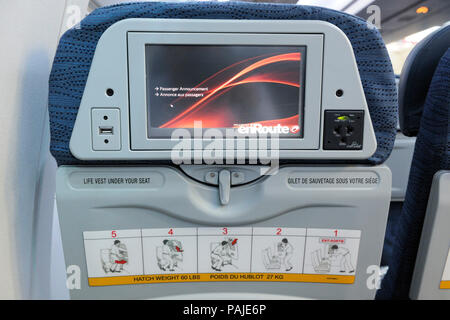 IFE screen in the seat-back of economy-class cabin seat with emergency-instructions on an Air Canada Boeing 767-300ER on flight number AC852 YYC-LHR - Stock Image