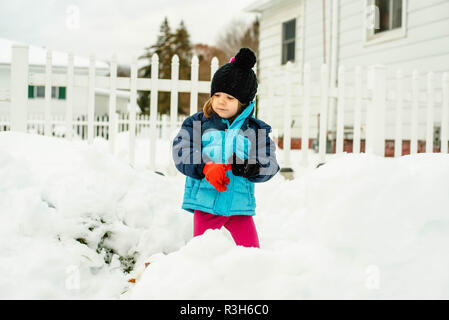 A little girl plays in the snow on a cold winter day in the United States. - Stock Image
