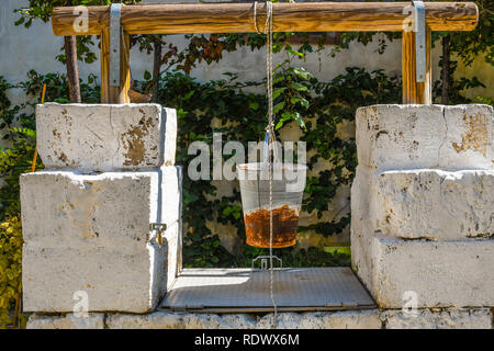 A medieval well with rusted bucket hanging from a rope in the garden of the Church of San Giovanni al Sepolcro in the city of Brindisi, Italy - Stock Image