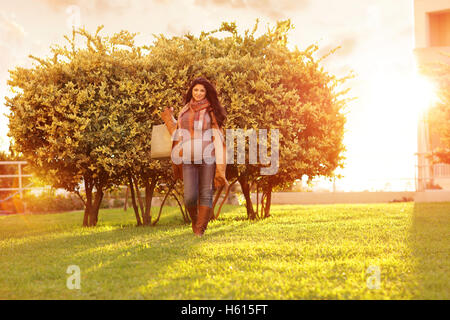 Happy pregnant woman after shopping, walking outdoors with shopping bags, warm sunny autumn day - Stock Image