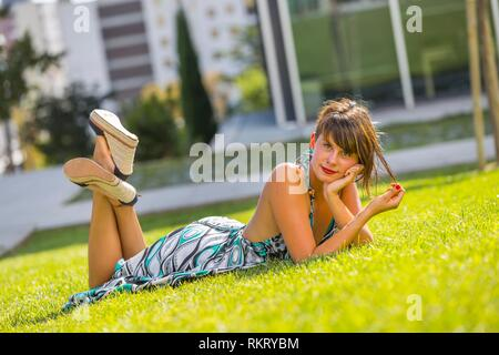 Young woman legs heels lying on stomach tummy belly on greenfield in park looking at camera - Stock Image