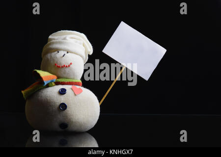Snowman figure on a black background holding an empty placard board with stick attached. A contrasty low key photograph. - Stock Image