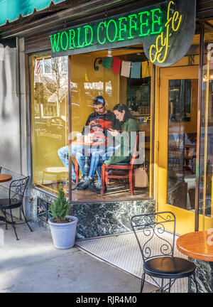 ASHEVILLE, NC, USA-2/3/19: A couple sits in front display window of coffee shop, at small table, each looking at smart phones. - Stock Image