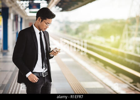 young asian hipster businessman with smartphone waiting at the train platform. Concept of wireless technology, public transport and business travel - Stock Image
