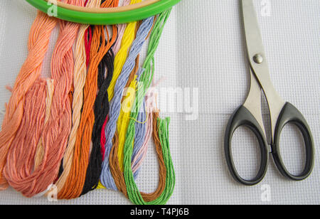 Scissors and bright colorful thread for embroidery thread on canvas. Handmade accessories on white background. Place for text, top view. - Stock Image