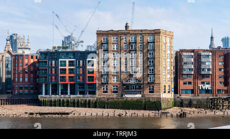 London, England, UK - April 15, 2010: Sun shines on apartment buildings and office blocks on the side of the River Thames in the City of London. - Stock Image