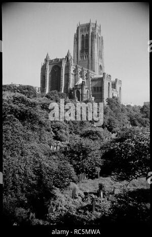 Cathedral Church of Christ, Liverpool, Merseyside, c1955-c1980. View of The Anglican Cathedral Church of Christ in Liverpool, with St James's Garden in the foreground, seen from the east road boundary of the garden, allowing the vantage to look below into the garden. The image shows the cathedral church sat on a rocky mass on the western side of St James's Gardens, with a wooded slope leading to a clearing with gravestones. The cathedral church is very young, built by Giles Gilbert Scott, assisted by architect GF Bodley, and opened in 1978. Scott's design for the cathedral was presented in 190 - Stock Image