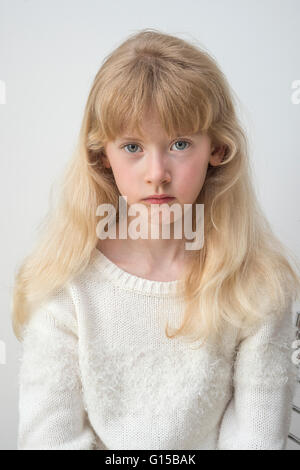 young eleven year old girl sad unhappy gloomy worried pensive thinking - Stock Image