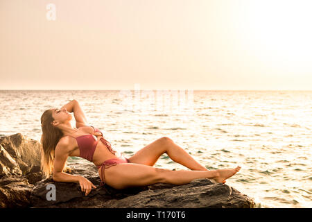 Perfect body brunette with bikni stay on the rocks for a perfec tan and sunbath enjoying the warm day of summer vacation at the sea - sexy girl in out - Stock Image