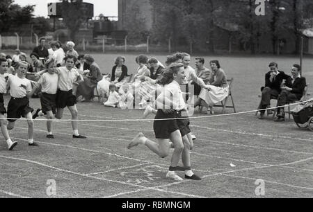 1950s, historial. sports day, primary school children taking part in a three-legged race, England, UK. Two girls with a ribbon tield around their legs aout to cross the finishing rope in a contest watched by spectators. - Stock Image