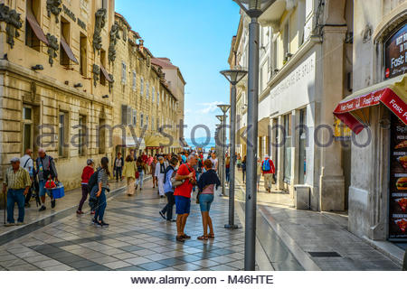 Tourists enjoy a sunny day just off the Riva Promenade at the harbor of the ancient city of Split Croatia on the - Stock Image