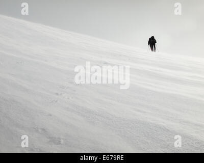 two men with heavy backpacks crossing a snowfield in a storm on snowshoes in  winter mountains with tracks in foreground - Stock Image