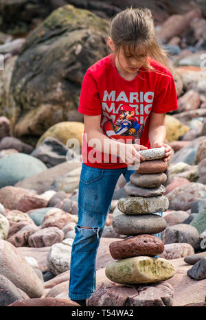 Dunbar, East Lothian, Scotland, UK. 21st Apr 2019. European stone stacking championship: Alijah, from Wales, builds a stone stack to win the Quantity competition for children under 15 years of age –- most stones balanced vertically - at Eye Cave beach on the second day which comprises 2 competitions, a 3 hour artistic challenge and a children's competition. The overall winner receives a trip to llano Earth Art Festival & World Stone Balancing competition in Texas in 2020. Credit: Sally Anderson/Alamy Live News - Stock Image